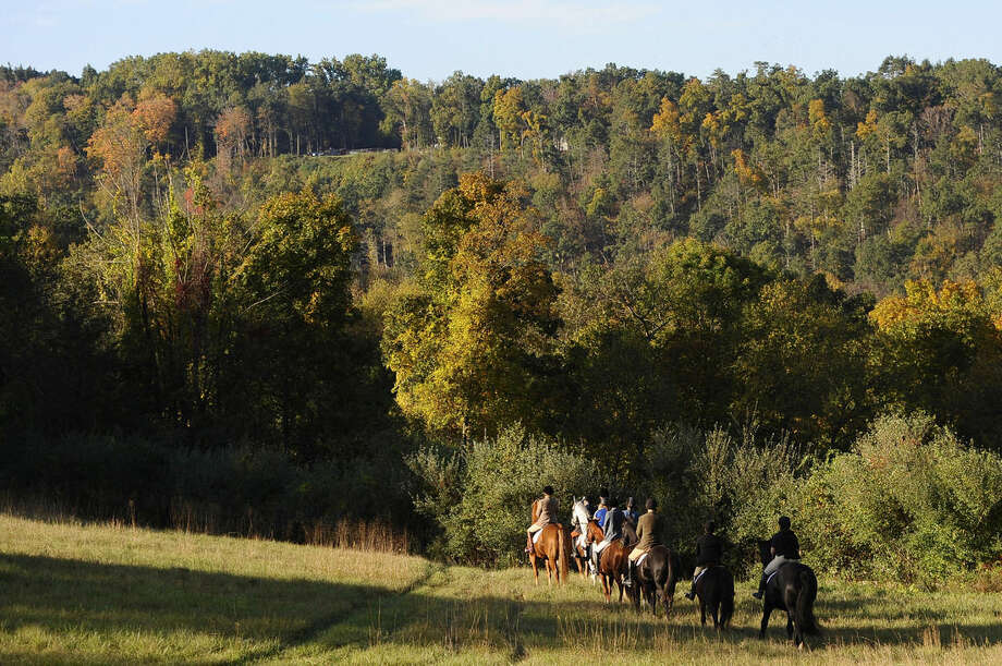 In this Wednesday, Oct. 8, 2014 photo, riders from Fairfield County Hounds head into the woods on a hunt in Bridgewater, Conn. The hunts require vast expanses of undeveloped land and permission to pass through from the property owners. The Bridgewater club, which was founded 90 years ago, relocated from nearby Newtown in the 1980s as rural property changed hands and some new owners refused to allow access. (AP Photo/Jessica Hill)