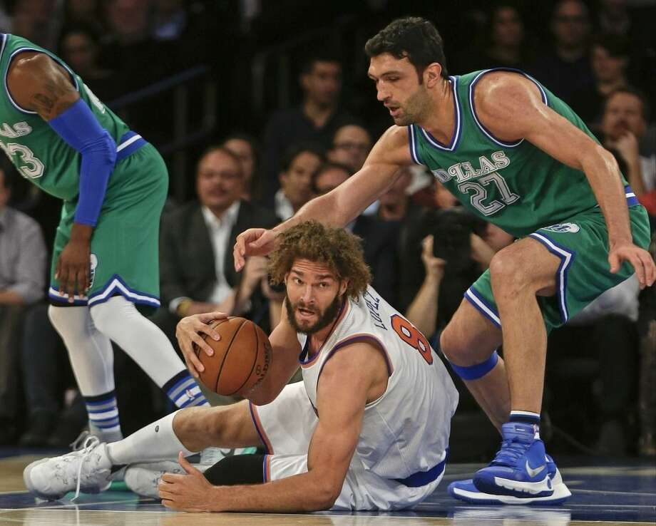 New York Knicks' Robin Lopez (8) looks to pass away from Dallas Mavericks' Zaza Pachulia (27) during the first half of an NBA basketball game Monday, Dec. 7, 2015, in New York. (AP Photo/Frank Franklin II)