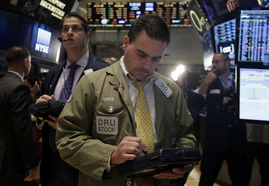 Trader Michael Iozzi, center, works on the floor of the New York Stock Exchange Tuesday, Oct. 14, 2014. U.S. stocks rose moderately in early trading Tuesday as investors pored over corporate earnings reports. (AP Photo/Richard Drew)