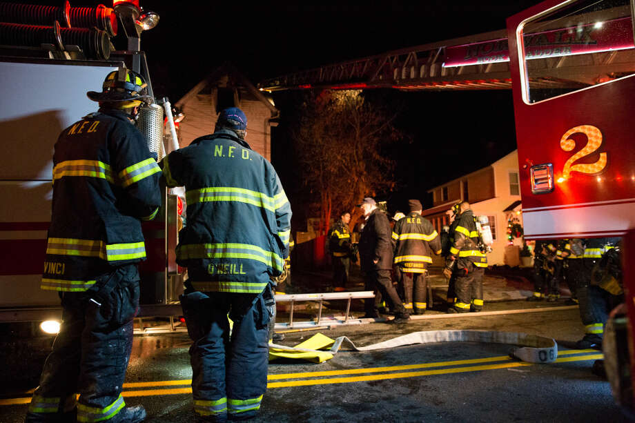 Hour photo/Chris Palermo. Norwalk Firefighters respond to a fire at 10 Cove Ave. Monday night. The fire started around 10:00 p.m. on the second floor before making its way up to the third floor which ultimately had to be gutted, while the first floor was flooded with water damage. The Red Cross was on sight helping residents, as well as one firefighter who twisted his knee battling the blaze.