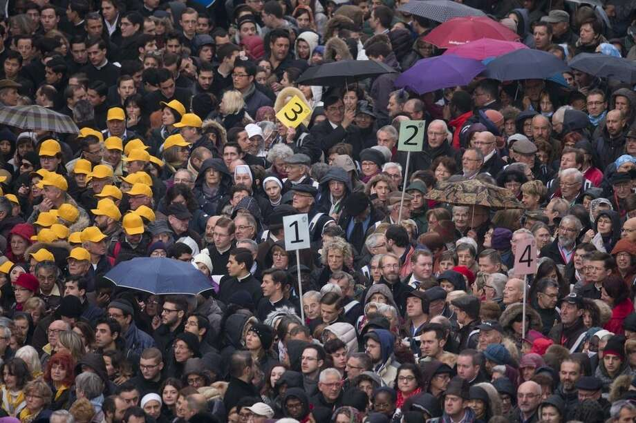 Faithful and pilgrims wait to enter in St. Peter's Square for the start of a Mass celebrated by Pope Francis on the occasion the opening of the Holy Door of St. Peter's Basilica, which formally starts the Jubilee of Mercy, at the Vatican, Tuesday, Dec. 8, 2015. (AP Photo/Alessandra Tarantino)