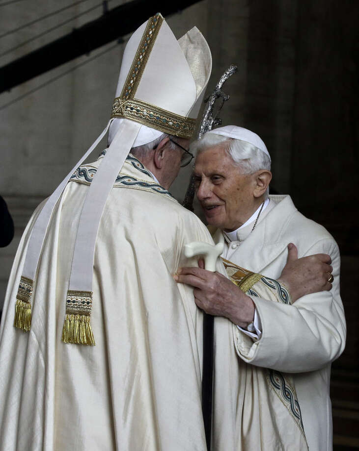 Pope Emeritus Benedict XVI, right, hugs Pope Francis in St. Peter's Basilica during the ceremony marking the start of the Holy Year, at the Vatican, Tuesday, Dec. 8, 2015. Pope Francis declared Tuesday that mercy trumps moralizing in the Catholic Church, as he opened a special Holy Year marked by unprecedented security aimed at thwarting a Paris-style attack at the Vatican. (AP Photo/Gregorio Borgia)