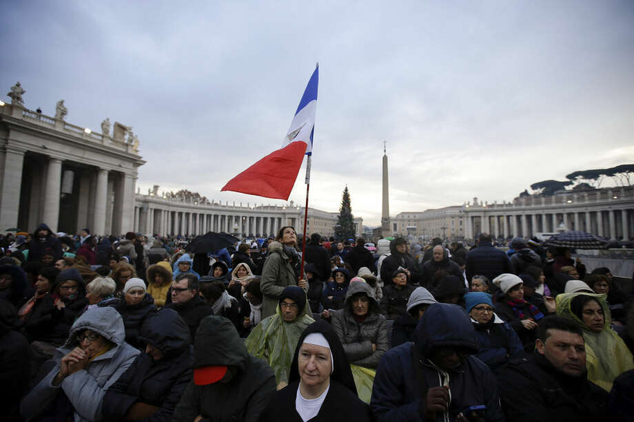 """A woman holds up French flag as she waits in St. Peter's Square for the start of a Mass celebrated by Pope Francis on the occasion the opening of the Holy Door of St. Peter's Basilica, at the Vatican, Tuesday, Dec. 8, 2015. Francis on Tuesday pushes open the huge bronze Holy Door to formally launch his yearlong """"revolution of tenderness"""" amid unprecedented security aimed at thwarting the threat of a Paris-style attack at the Vatican. (AP Photo/Gregorio Borgia)"""
