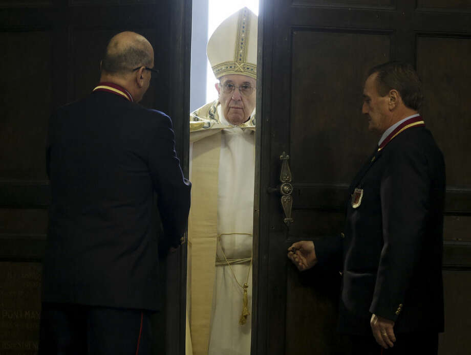 Pope Francis pushes open the Holy Door of St. Peter's Basilica, formally launching the Holy Year of Mercy, at the Vatican, Tuesday, Dec. 8, 2015. The 12-month jubilee emphasizes what has become the leitmotif of his papacy: to show the merciful and welcoming side of a Catholic Church more often known for its moralizing and judgment. (AP Photo/Andrew Medichini)