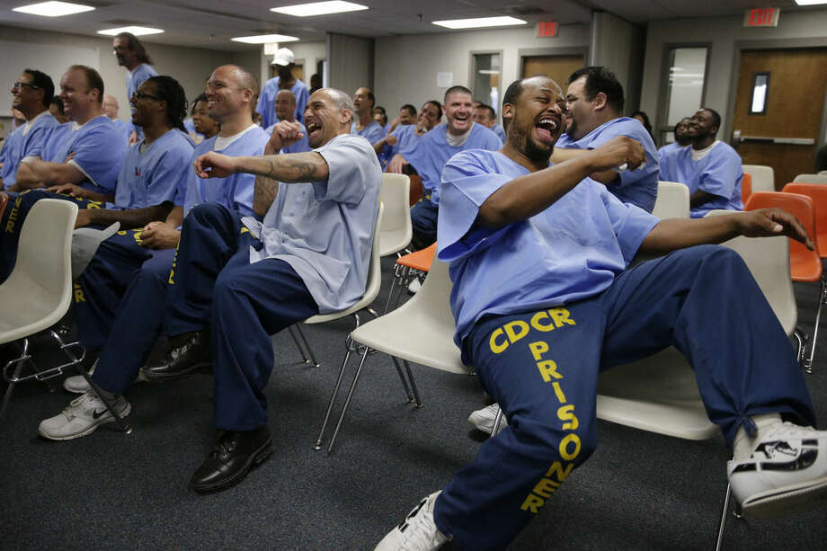 In this Sept. 30, 2014, photo, inmates laugh while watching inmate actors perform during an Actors' Gang Prison Project workshop, an outreach program led by actor Tim Robbins, at the California Rehabilitation Center in Norco, Calif. The nonprofit acting program is expanding thanks to its slice of a $2.5 million arts pilot project from the California Department of Corrections and Rehabilitation. The funding will bring state-funded arts of all kinds to inmates at more than a dozen prisons for the first time since California's prison arts network withered more than a decade ago. (AP Photo/Jae C. Hong)