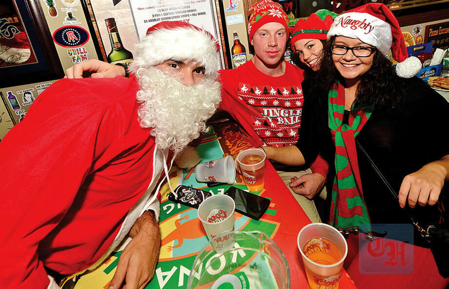 Matt Paz, Mitchell Paz, Robyn Bothwell and Dana Tyle grab a beer at Brickhouse during the 2015 Stamford SantaCon pub crawl Saturday.