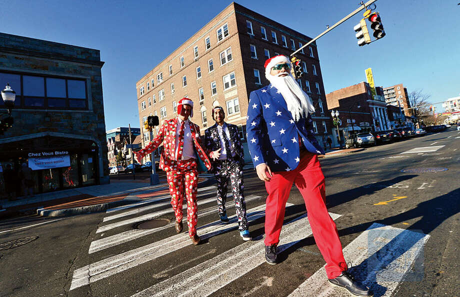 PJ Landi, Steve Dryer and Rick Caban move to the next establishment on Bedford Street during the 2015 Stamford SantaCon pub crawl Saturday.