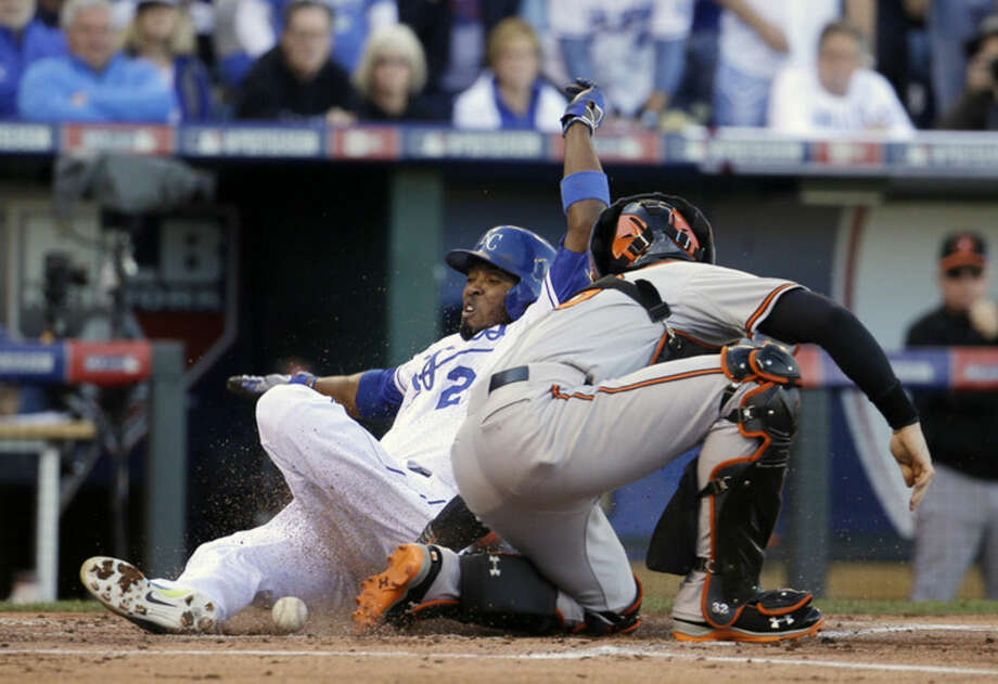 Kansas City Royals' Alcides Escobar scores against Baltimore Orioles catcher Caleb Joseph during the first inning of Game 4 of the American League baseball championship series Wednesday, Oct. 15, 2014, in Kansas City, Mo. (AP Photo/Charlie Riedel)