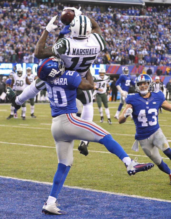 New York Jets wide receiver Brandon Marshall (15) catches a pass of a touchdown in front of New York Giants' Prince Amukamara (20) and Craig Dahl (43) during the second half of an NFL football game Sunday, Dec. 6, 2015, in East Rutherford, N.J. (AP Photo/Bill Kostroun)