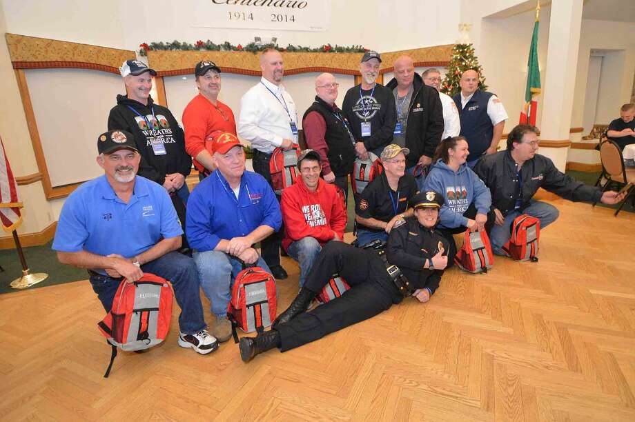 Hour Photo/Alex von Kleydorff Janine Roberts Police Chief, Westbrook Maine poses with the drivers for a group photo with the Wreaths Across America group that stopped in Norwalk for dinner at The St Ann Club on their way to Arlington National Cemetery.