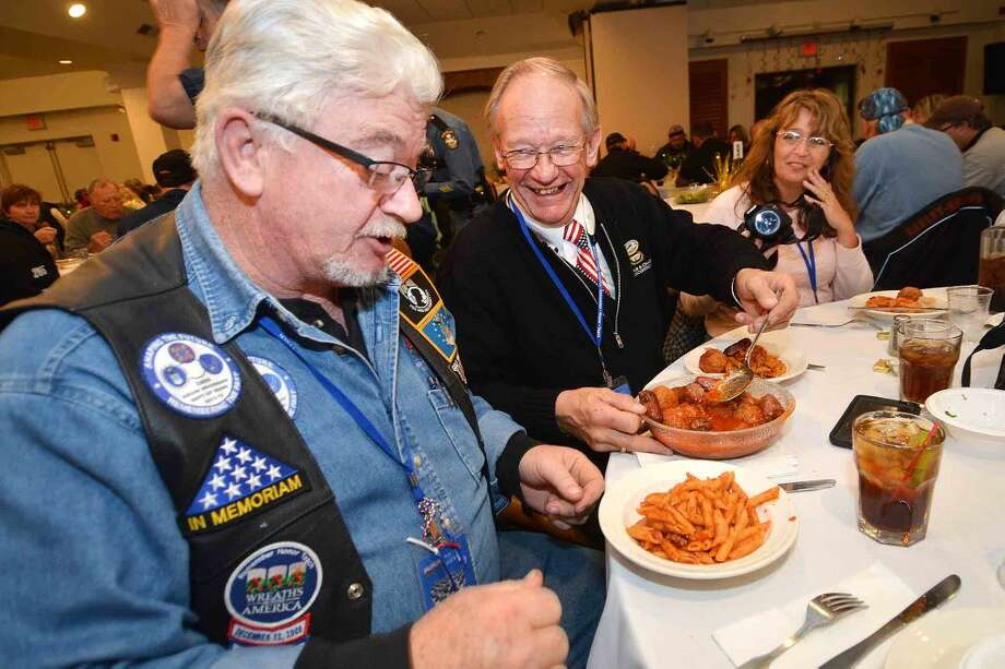 Hour Photo/Alex von Kleydorff Volunteer drivers Dennis Farnum and Kevin Woodward gets some meatballs and sausage moving around the table as more than 100 volunteers with the Wreaths Across America group stopped in Norwalk for dinner at The St Ann Club on their way to Arlington National Cemetery.