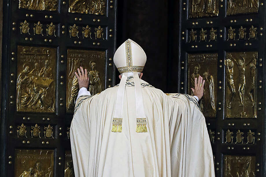 Pope Francis pushes open the Holy Door of St. Peter's Basilica, formally launching the Holy Year of Mercy, at the Vatican, Tuesday, Dec. 8, 2015. Pope Francis pushed open the great bronze doors of St. Peter's Basilica on Tuesday to launch his Holy Year of Mercy, declaring that mercy trumps moralizing in his Catholic Church. (AP Photo/Gregorio Borgia)
