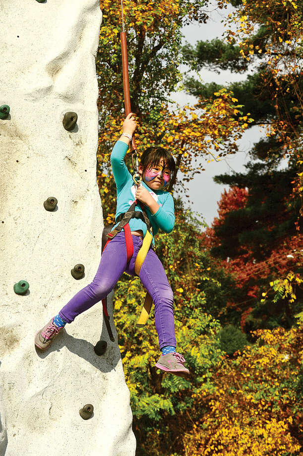 Hour photo / Erik Trautmann Wolfpit Elementary School 2nd grader Victoria Shin tries the climbing wall during her school 's annual Pumpkin Festival Saturday.