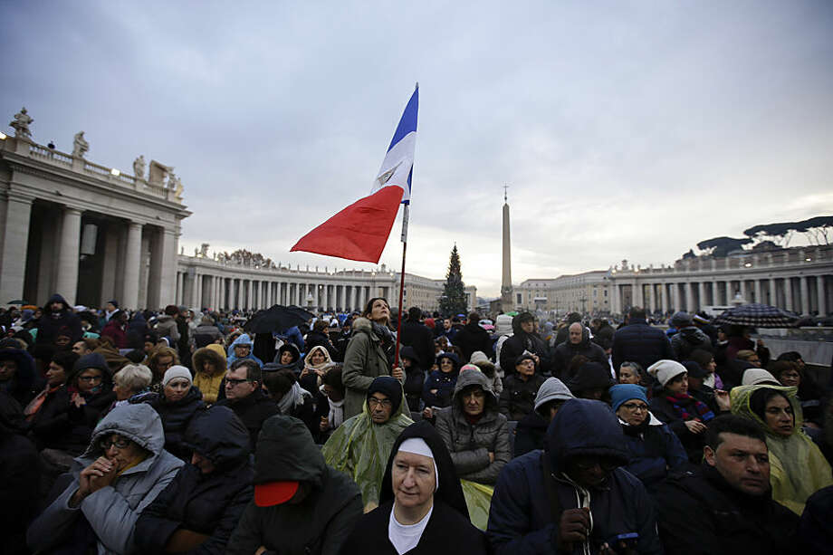 "A woman holds up French flag as she waits in St. Peter's Square for the start of a Mass celebrated by Pope Francis on the occasion the opening of the Holy Door of St. Peter's Basilica, at the Vatican, Tuesday, Dec. 8, 2015. Francis on Tuesday pushes open the huge bronze Holy Door to formally launch his yearlong ""revolution of tenderness"" amid unprecedented security aimed at thwarting the threat of a Paris-style attack at the Vatican. (AP Photo/Gregorio Borgia)"