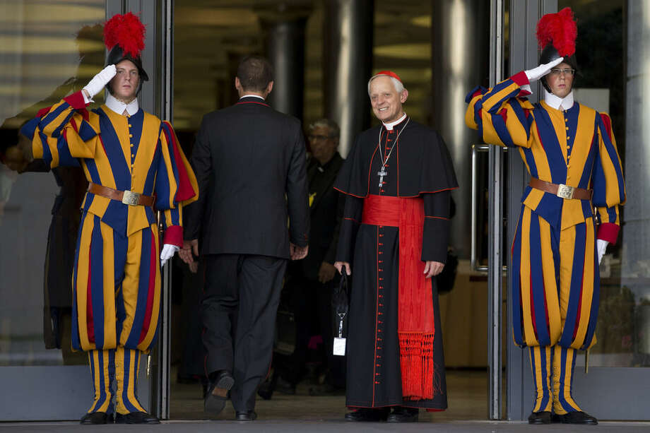 "Cardinal Donald Wuerl, Archbishop of Washington, is saluted by two Swiss guards as he arrives to attend an afternoon session of a two-week synod on family issues at the Vatican, Saturday, Oct. 18, 2014. Catholic bishops predicted widespread approval Saturday of a revised document laying out the church's position on gays, sex, marriage and divorce, saying the report is a ""balanced"" reflection of church teaching and pastoral demands. The final report of the two-week meeting of bishops will be voted on later Saturday. (AP Photo/Andrew Medichini)"