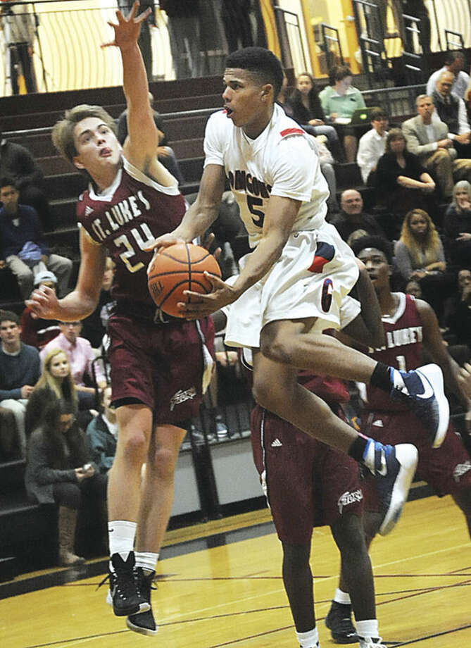 Greens Farms Academy guard Elvin Rodriguez, right, drives past the defense of St. Luke's John Wisdon during Tuesday's Fairchester Athletic Association boys basketball game in New Canaan. St. Luke's won the game, 89-37, over an injury-riddled GFA team.Hour photo/Matthew Vinci