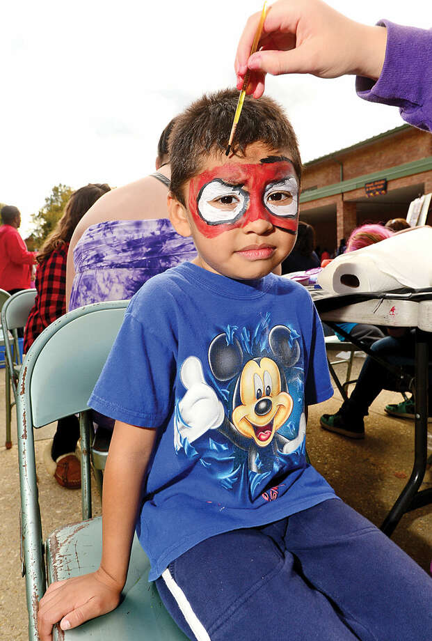 Hour photo / Erik Trautmann Wolfpit Elementary School kindergartner Jovan Sandoval gets his face painted during his school 's annual Pumpkin Festival Saturday.