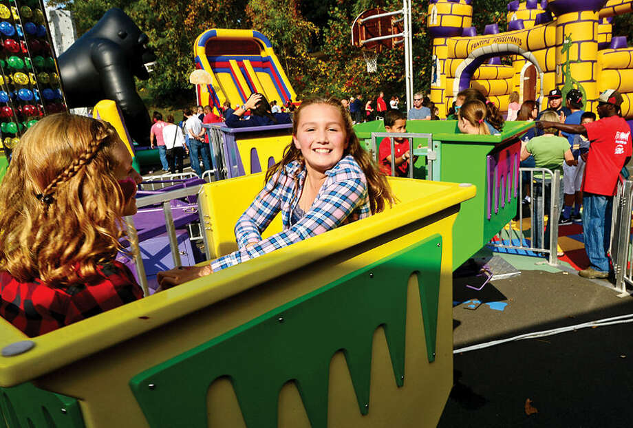 Hour photo / Erik Trautmann Brin Renwick and her friend Dylan Ackerman, both 11, ride on of the attractions at the Wolfpit Elementary School annual Pumpkin Festival Saturday.