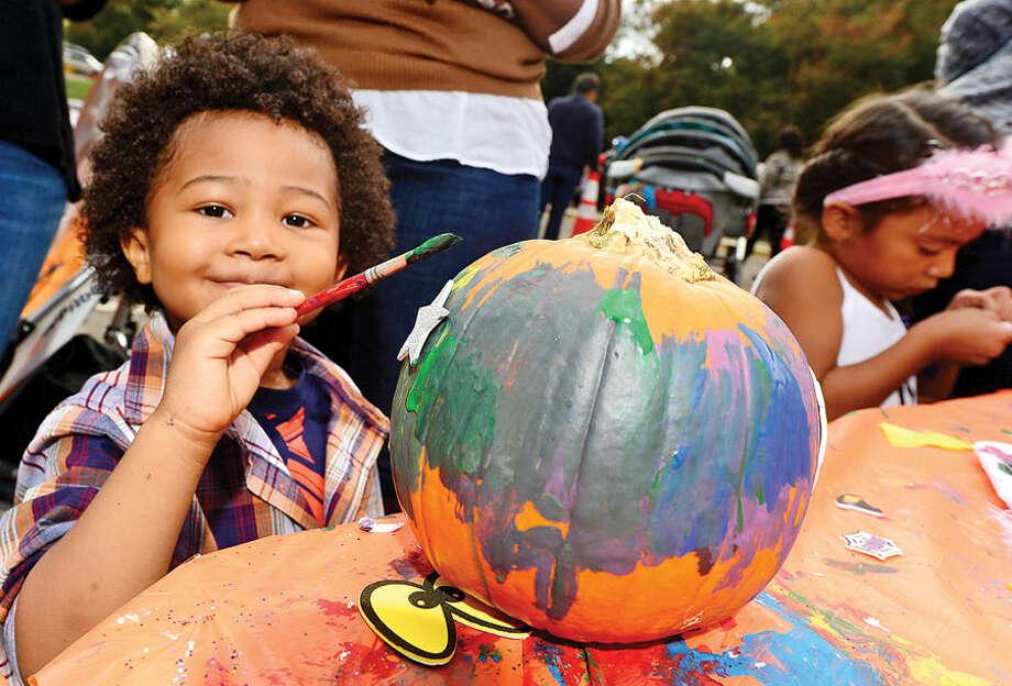 Hour photo / Erik Trautmann 2 year old Caleb Goodwin paints a pumpkin during Wolfpit Elementary School's annual Pumpkin Festival Saturday.