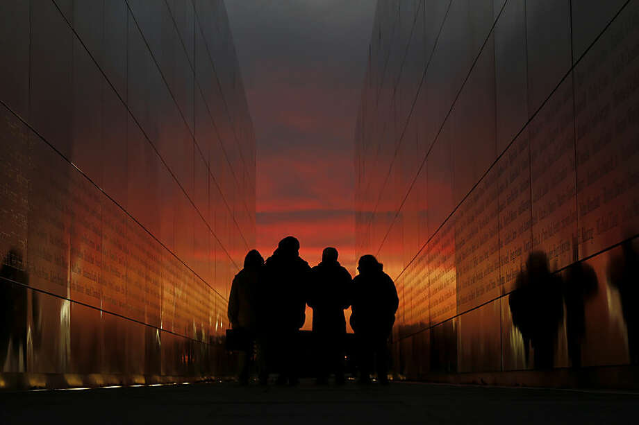People walk through the Empty Sky memorial during sunset at Liberty State Park, Tuesday, Dec. 8, 2015, in Jersey City, N.J. (AP Photo/Julio Cortez)