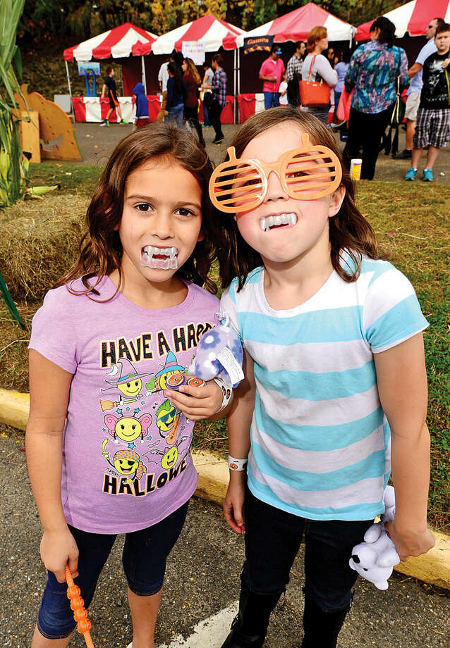 Hour photo / Erik Trautmann Wolfpit Elementary School 2nd graders Emily Retsaino and Ally Lanzarotto attend their school 's annual Pumpkin Festival Saturday.