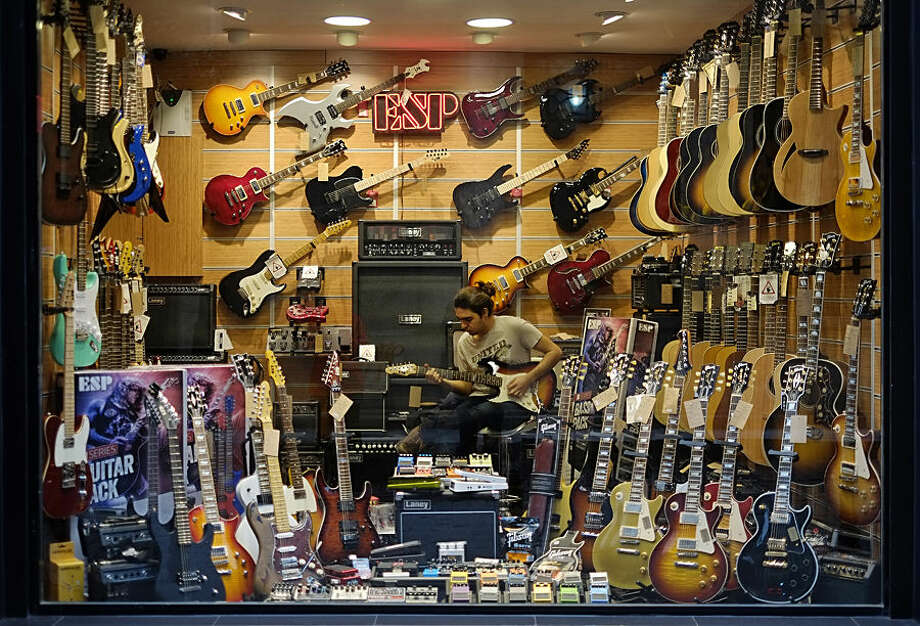 A man plays a guitar inside a musical instrument shop near central Istanbul's Istiklal Avenue, the main shopping road of Istanbul, Tuesday Dec. 8, 2015. (AP Photo/Lefteris Pitarakis)
