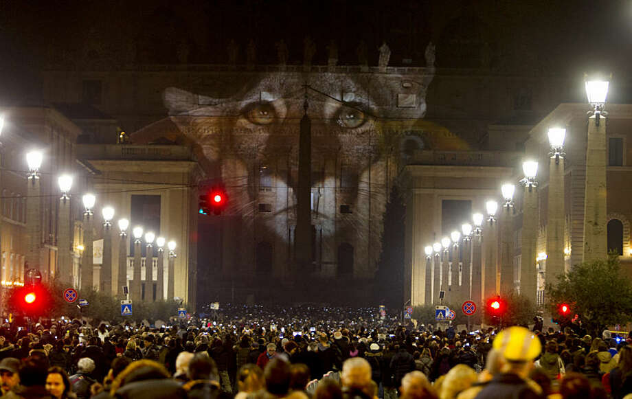 People gather to watch images projected on the facade of St. Peter's Basilica, at the Vatican, Tuesday, Dec. 8, 2015. The Vatican is lending itself to environmentalism with a special public art installation timed to coincide with the final stretch of climate negotiations in Paris. On Tuesday night, the facade of St. Peter's Basilica has been turned into a massive backdrop for a photo light show about nature organized by several humanitarian organizations. Organizers offered the installation as a gift to Francis to mark his Holy Year of Mercy, which began Tuesday. (AP Photo/Riccardo De Luca)