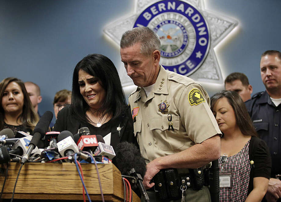 San Bernardino County Sheriff John McMahon, right, comforts dispatcher Michelle Rodriguez during a news conference with the first responders who were at the scene of last week's fatal shooting at the Inland Regional Center, Tuesday, Dec. 8, 2015, in San Bernardino, Calif. (AP Photo/Jae C. Hong)