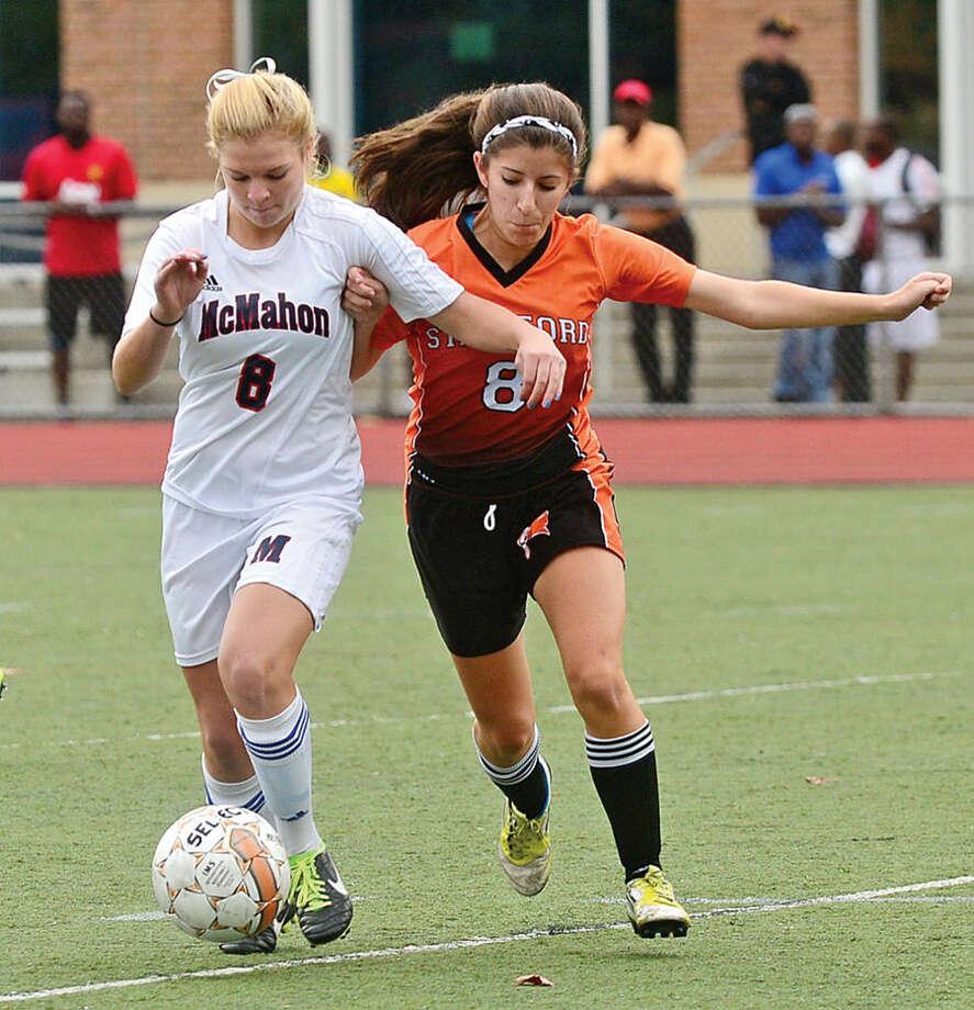 Hour photo / Erik Trautmann Brien McMahon High School Senator # 8 Madeline Dunn battles Stamford's # 8 Nicole Cadavid during their girls soccer match Saturday in Norwalk.