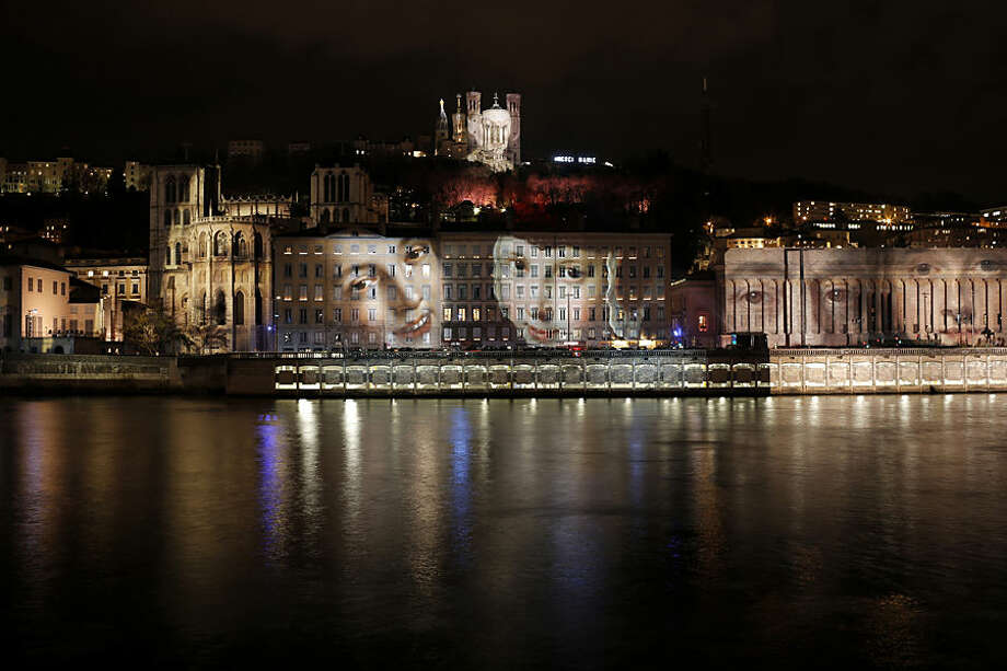 A projection of French artist Daniel Knipper, named 'Regards', is displayed on buildings of Lyon, central France, Tuesday, Dec. 8, 2015, as part of a tribute to the 130 victims of the attacks in Paris. Each year, millions of visitors come into the city to watch the Festival des Lumieres, and this year the Lyon municipality has decided to cancel the festival to express solidarity with the victims. (AP Photo/Laurent Cipriani)