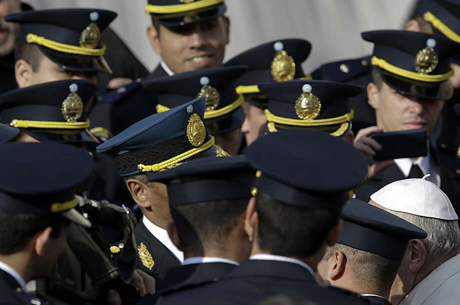 Pope Francis, right, meets with a group of Argentinean policemen in St. Peter's Square during the weekly general audience, at the Vatican, Wednesday, Dec. 9, 2015. (AP Photo/Gregorio Borgia)