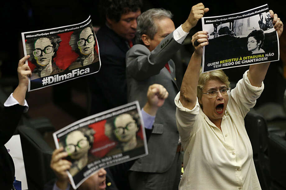 "Lawmakers who support President Dilma Rousseff hold up pictures of the leader when she was a political prisoner, which read in Portuguese: ""Dilma stay"", during a lower house session to nominate representatives for a special commission that will determine whether impeachment proceedings against Rousseff will go to a full vote in the house in Brasilia, Brazil, Tuesday, Dec. 8, 2015. The proceedings were introduced last week, citing a court's finding that Rousseff's administration violated fiscal responsibility laws by using money from state-run banks to fill budget gaps and pay for social programs. (AP Photo/Eraldo Peres)"