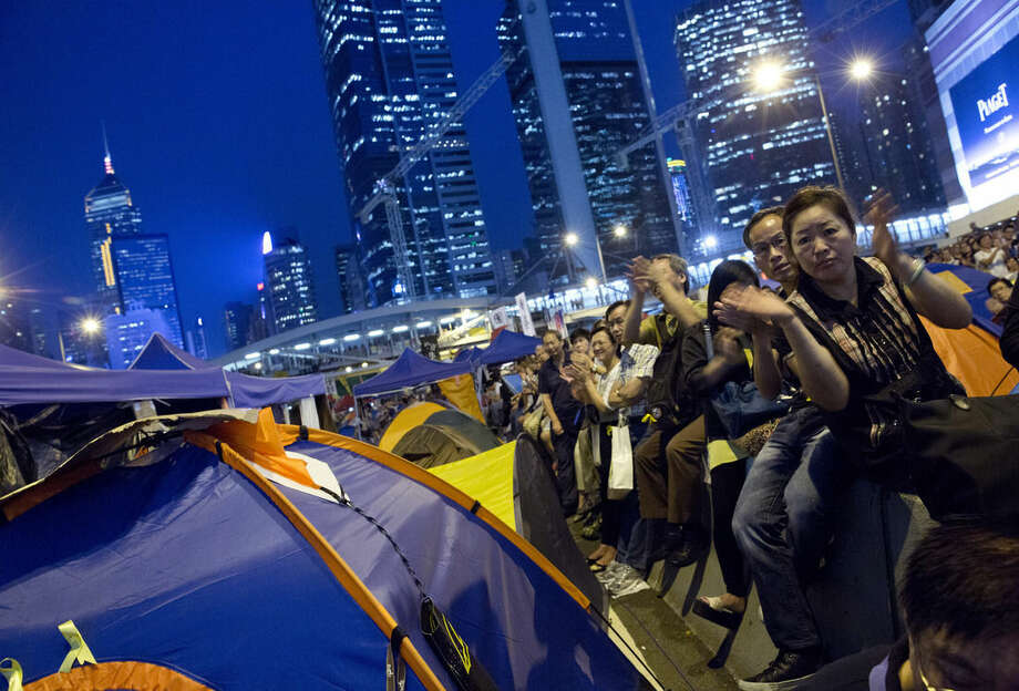 Pro-democracy protesters cheer as they listen to a student leader during a live TV showing talks between Hong Kong government officials and students at an occupied area outside the government headquarters in Hong Kong's Admiralty district Tuesday, Oct. 21, 2014. Hong Kong officials and student leaders hold talks Tuesday to try to end pro-democracy protests that have gripped the southern Chinese city for more than three weeks, though chances of success are slim given the vast differences between the two sides. (AP Photo/Vincent Yu)