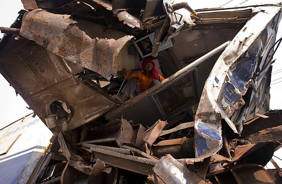 A railway trackman looks for belongings of the driver after two trains collided at Janauli in the northern state of Haryana, India, Tuesday, Dec. 8, 2015. The driver of one of the trains was killed and dozens were injured in the accident 60 kilometers (35 miles) south of New Delhi. (AP Photo/Saurabh Das)