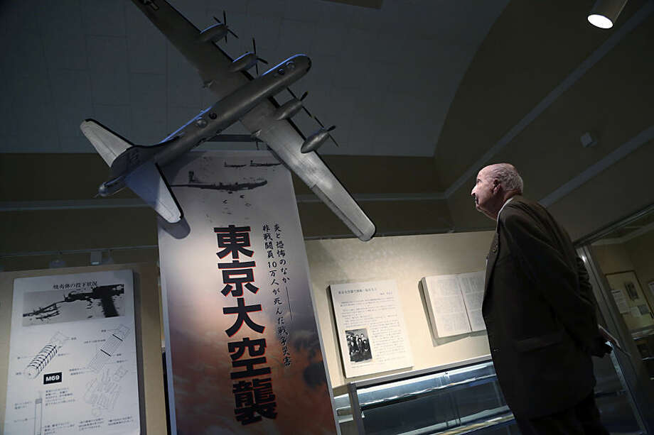 "Fiske Hanley of Fort Worth, TX, an American World War II veteran who took part in firebombing of Tokyo and was later held captive by the Japanese 70 years ago, watches scale model of B-29 bomber at the Center of the Tokyo Raids and War Damage in Tokyo Wednesday, Dec. 9, 2015. Hanley, 95, was on a B-29 as engineering crew in the March 10, 1945 firebombing that nearly destroyed eastern Tokyo, with overnight death toll exceeding 100,000. Hanley is also a victim of brutality by Japan's ""kempeitai"" military police during his captivity after his B-29 crashed.(AP Photo/Eugene Hoshiko)"