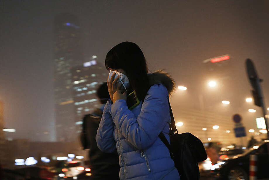 A woman covers her face with a mask as she rushes to a subway station on a heavily polluted day in Beijing Tuesday, Dec. 8, 2015. Beijing's red alerts for smog are as much about duration as they are about severity of pollution forecasts. The forecasting model must predict three or more days of smog with levels of 300 or higher on the city's air quality index - which typically would include having levels of dangerous PM 2.5 particles of about 10 times the safe level. (AP Photo/Andy Wong)