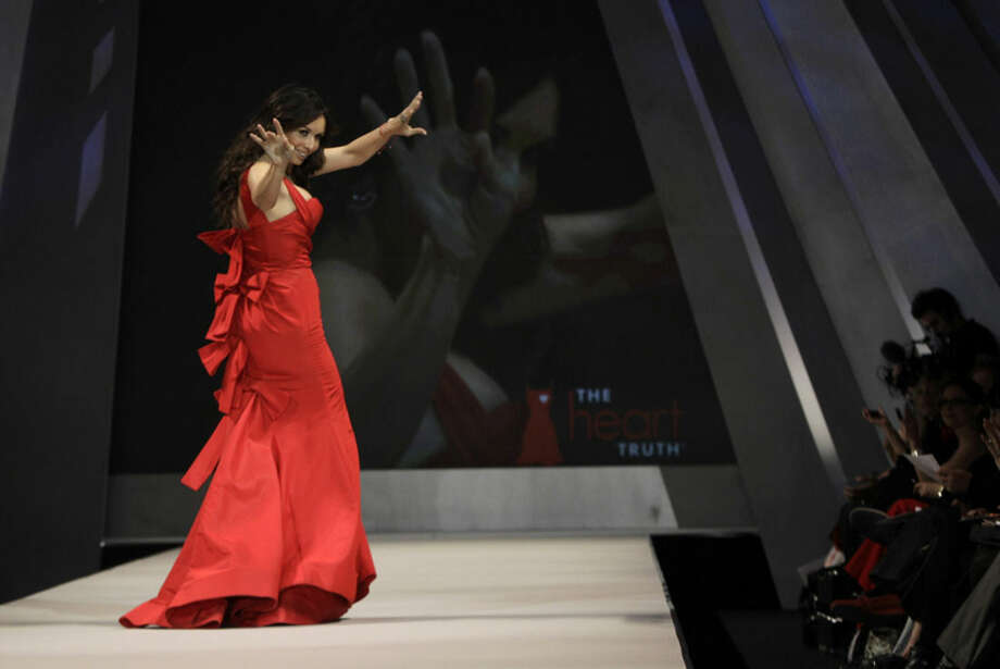 FILE - In this Feb. 8, 2012, file photo, actress Giselle Bloindet waves to the crowd as she models Oscar de la Renta during the Heart Truth Red Dress fashion show in New York. The designer, who died Monday, Oct. 20, 2014, at 82, shaped American couture half a century ago when it emerged as a serious rival to European fashion designers. (AP Photo/Kathy Willens, File)