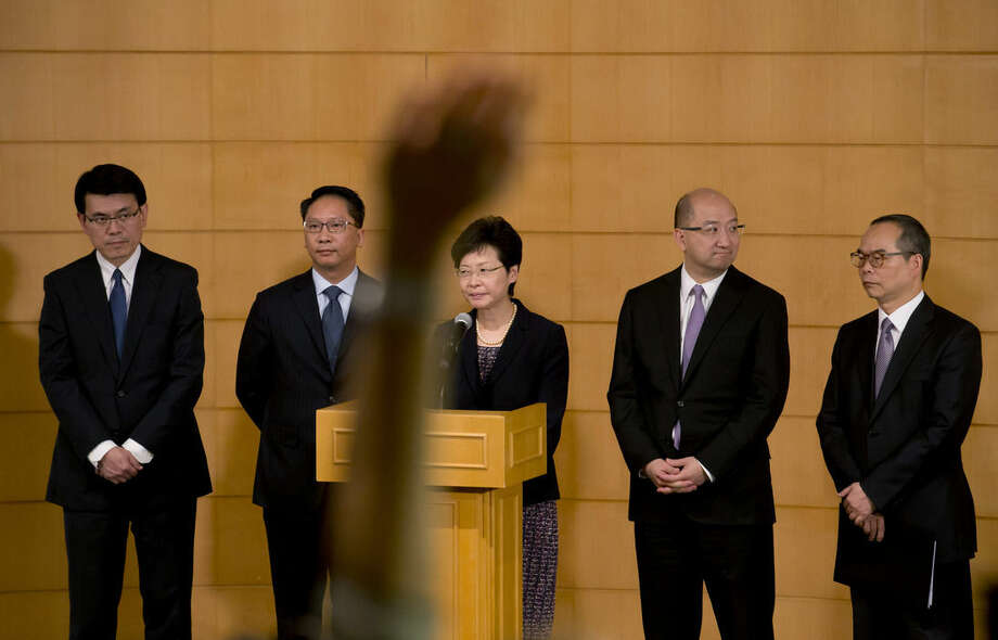 A reporter raises a hand to cast a question as Hong Kong government officials, from right, Undersecretary of the Constitutional and Mainland Affairs Bureau Lau Kong-wah, Secretary for Constitutional and Mainland Affairs Raymond Tam, Chief Secretary for Administration Carrie Lam, Secretary for Justice Rimsky Yuen and Chief Executive's Office Director Edward Yau Tang-wah attend a news conference after their talks on constitutional development with the student leaders in Hong Kong Tuesday, Oct. 21, 2014. Hong Kong student leaders and government officials held talks Tuesday to end pro-democracy protests now in their fourth week even as the city's Beijing-backed leader reaffirmed his unwillingness to compromise on the activists' key demand. (AP Photo/Kin Cheung)