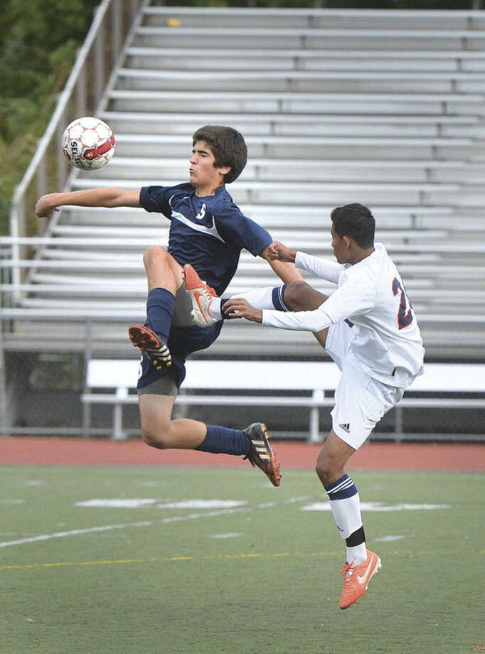 Hour photo/Alex von KleydorffStaples' Jerrett Rende jumps in front of McMahon's Edison Pena to keep the ball away from him Tuesday. Staples won 1-0.