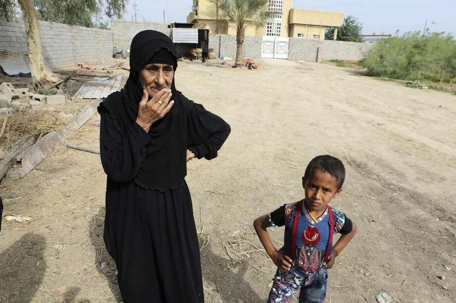 In this Saturday, Oct. 18, 2014 photo, a local farmer stands in her family farm in the Abu Ghraib suburb of Baghdad, Iraq. After the revelation of prisoner abuse at the hands of U.S. troops following the 2003 invasion, Abu Ghraib became the scene of brutal insurgent attacks. Al-Qaida in Iraq, which eventually would morph into the group now known as Islamic State, targeted tribal leaders opposed to its ideology throughout Iraq's Sunni heartland in the years that followed. (AP Photo/Karim Kadim)
