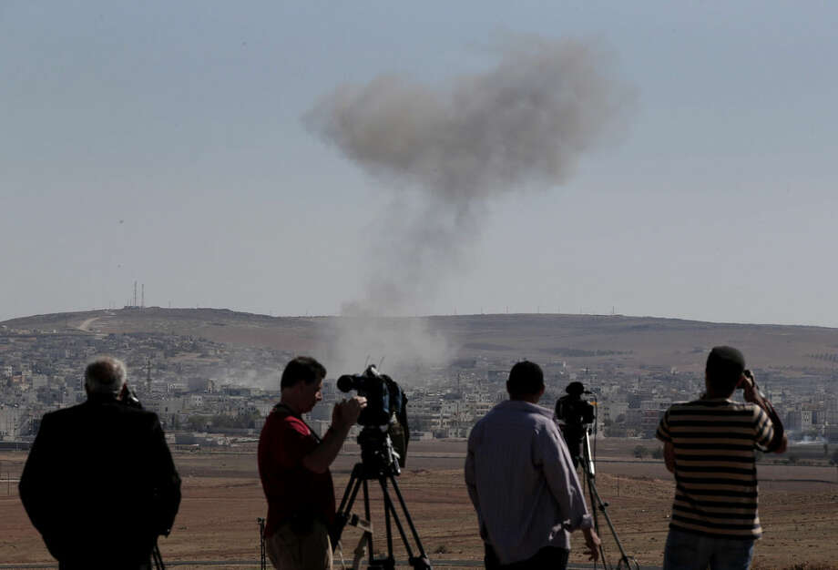 Smoke from an airstrike by the US-led coalition rises in Kobani, Syria, as members of the media film from a hilltop on the outskirts of Suruc, at the Turkey-Syria border, Wednesday, Oct. 22, 2014. Kobani, also known as Ayn Arab, and its surrounding areas, has been under assault by extremists of the Islamic State group since mid-September and is being defended by Kurdish fighters. (AP Photo/Lefteris Pitarakis)
