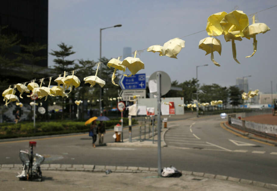Yellow paper umbrellas made by pro-democracy protesters are hung on a wire in an occupied area outside government headquarters in Hong Kong's Admiralty district Wednesday, Oct. 22, 2014. The student-led protests are rooted in growing discontent among young people about poor economic prospects amid one of the world's biggest wealth gaps. The protesters want Hong Kong's government to abandon a requirement by China's legislature for a committee to screen candidates for inaugural 2017 elections for the top leader. They say it gives the city's pro-Beijing elite too much say. (AP Photo/Vincent Yu)