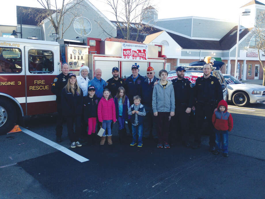 "The Wilton police and fire departments teamed up with the Toy Chest to take the Toys for Tots collection drive to another level this year. The ""Stuff a Cruiser"" event was held Sunday at 21 River Road in the Stop and Shop plaza. Pictured are some of the folks who volunteered at Sunday's event."