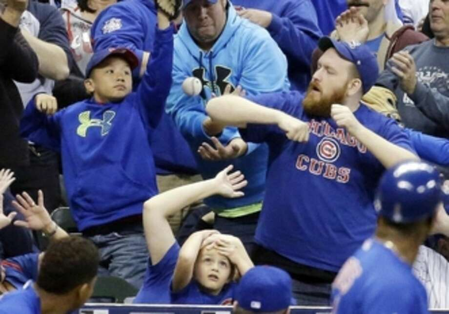 FILE - In this Oct. 2, 2015, file photo, fans go after a foul ball hit by Chicago Cubs' Dexter Fowler during the third inning of a baseball game against the Milwaukee Brewers, in Milwaukee. Major League Baseball has recommended teams have protective netting between the dugouts for any field-level seats within 70 feet of home plate. The guidelines were issued Wednesday, Dec. 9, 2015, at the winter meetings following a season in which several fans were injured by foul balls, prompting MLB to study fan safety.(AP Photo/Morry Gash, File)