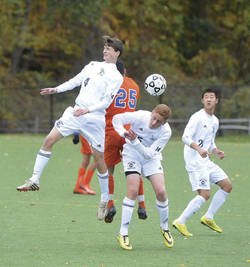 Hour Photo/Alex von KleydorffWilton's Daniel Jensen, left, and Max Najarian, center, keep the ball from Danbury as Michael Lynch looks on during Wednesday's game in Wilton.