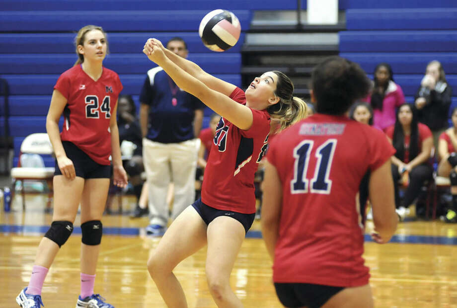 Hour photo/John NashBrien McMahon's Sierra Crial, center, bumps the ball back toward the net as teammates Claire Kostohryz, left, and Jsseline Zuniga look on.