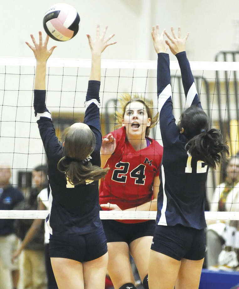 Hour photo/John NashBrien McMahon's Claire Kostohryz, center, sends down a kill between Wilton blockers Claire McCullough, left, and Carly Lovallo.