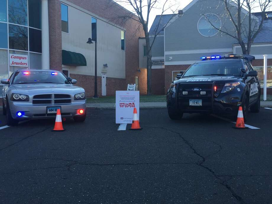 """The Wilton police and fire departments teamed up with the Toy Chest to take the Toys for Tots collection drive to another level this year. The """"Stuff a Cruiser""""event was held Sunday at 21 River Road in the Stop and Shop plaza."""