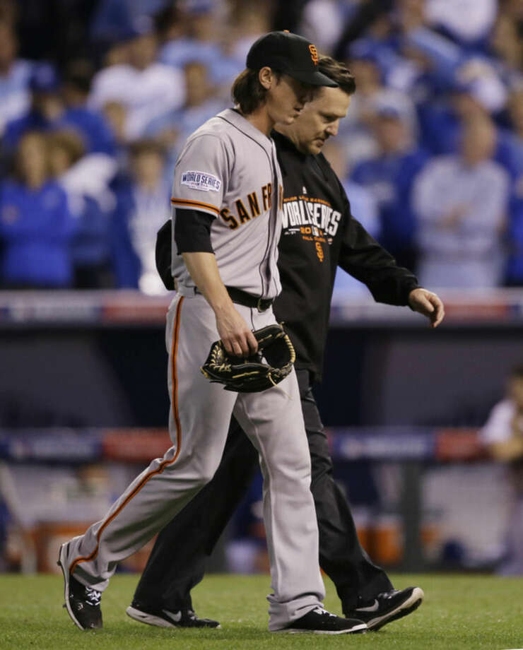 San Francisco Giants pitcher Tim Lincecum is escorted off the field during the eighth inning of Game 2 of baseball's World Series against the Kansas City Royals Wednesday, Oct. 22, 2014, in Kansas City, Mo. (AP Photo/Charlie Neibergall)
