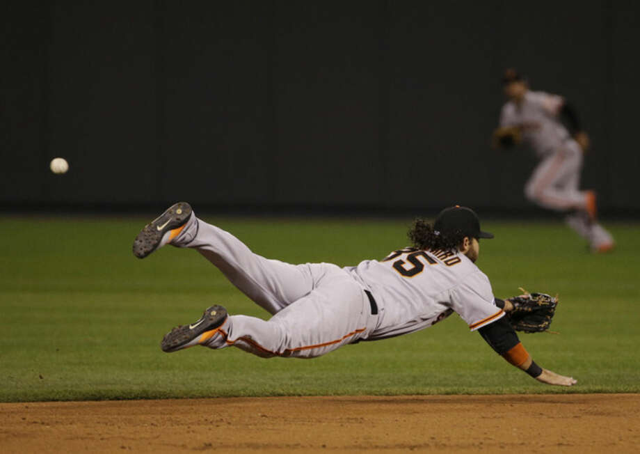 San Francisco Giants shortstop Brandon Crawford can not make a catch on an RBI single by Kansas City Royals Billy Butler during the first inning of Game 2 of baseball's World Series Wednesday, Oct. 22, 2014, in Kansas City, Mo. (AP Photo/Matt Slocum)
